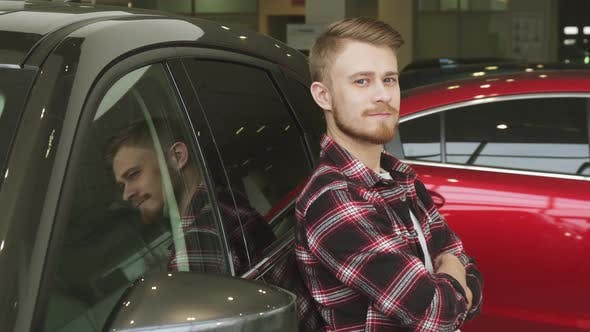 Thumbnail for Handsome Man Showing Thumbs Up Leaning on a New Car at the Dealership