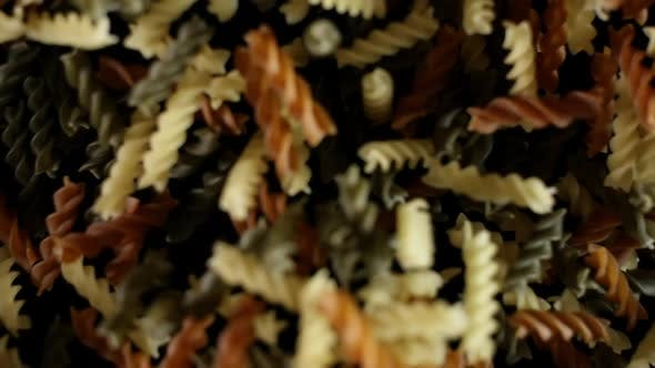 Cover Image for Rotini Pasta Macaroni Flies After Being Exploded. Pile of Multicolored Pasta Bouncing Black Bg