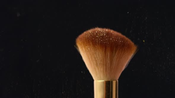 Thumbnail for Sweeping Gold Shimmer Powder from Makeup Brush on Black Background