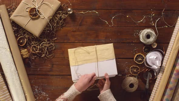 Cover Image for Woman Decorating Christmas Gift Box with Dried Orange Slice and Rope