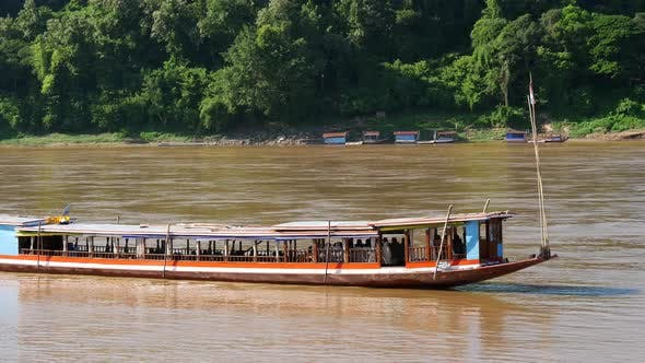 Thumbnail for Long-tail boat moving at the current at the Mekong river in Luang Prabang