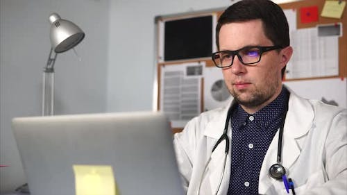 Doctor of a Private Clinic Prints the Text on the Laptop in His Private Office
