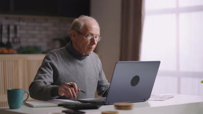 Old Man is Working with Laptop at Home Calculating By Calculator and Sending Message By Laptop