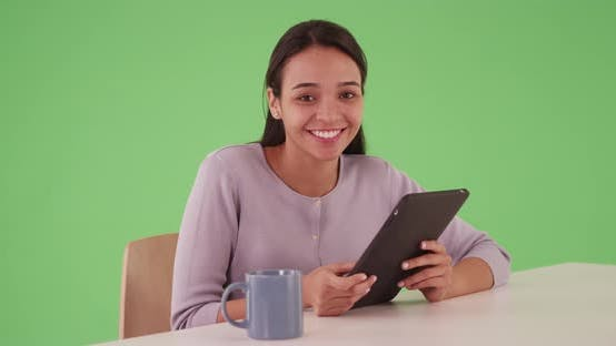 Thumbnail for Latina business professional smiling at desk with tablet computer on greenscreen