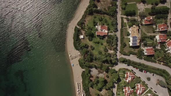 Thumbnail for - Aerial Shot of Resort Town with Cottages on Sea Coast, Greece