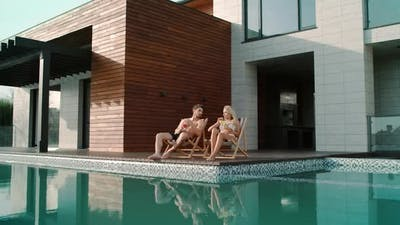 Rich Couple Relaxing Near Swimming Pool Atprivate House