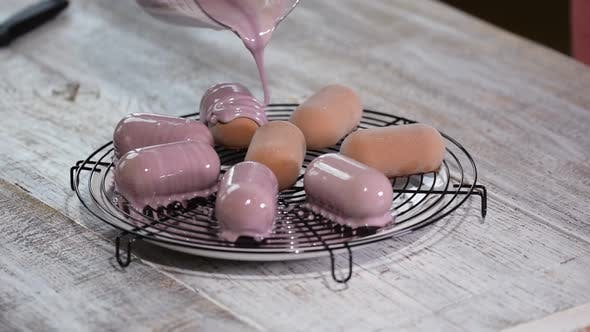 Thumbnail for Pouring mousse cake with mirror glaze. Glazing french dessert at confectionery