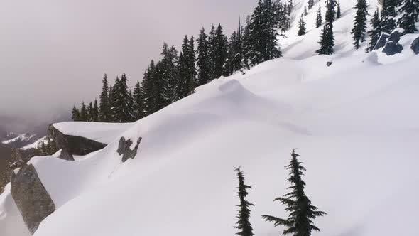 Thumbnail for Snowy Mountain Ridge Snowshoe Aerial Over Fresh Untouched Powder