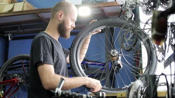 Thumbnail for Man repairing a bike wheel