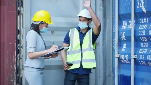Businesswoman and Foreman checking container