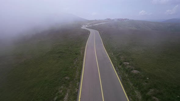 Tracking Drone Shot of Empty Road in Fog Foggy Morning in Rural Area Highway Surrounded By Green