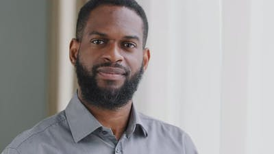 Smiling Bearded Millennial African Guy Professional Looking at Camera