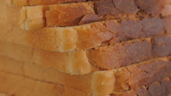 Thumbnail for Toast bread pieces arranged on table 4K 2160p UltraHD tilting footage - Toast bread on wooden table