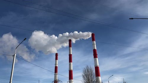 White smoke from the chimneys of an industrial plant against a blue sky.