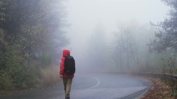 Thumbnail for Male Tourist in Red Raincoat Walking on Foggy Wet Road