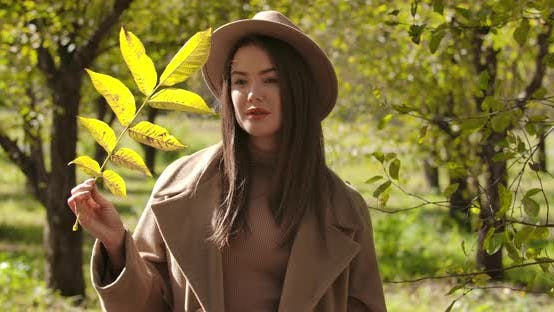 Thumbnail for Thoughtful Caucasian Girl in Brown Hat Standing in the Autumn Park and Holding a Tree Branch. Pretty