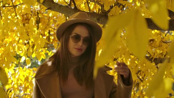 Thumbnail for Charming Young Caucasian Girl in Sunglasses and Hat Posing in Sunlight in the Autumn Park. Beautiful