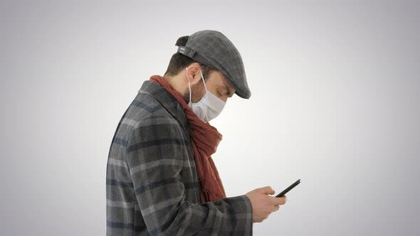Thumbnail for Stylish Man in Medical Mask Walking and Using Smart Phone on Gradient Background