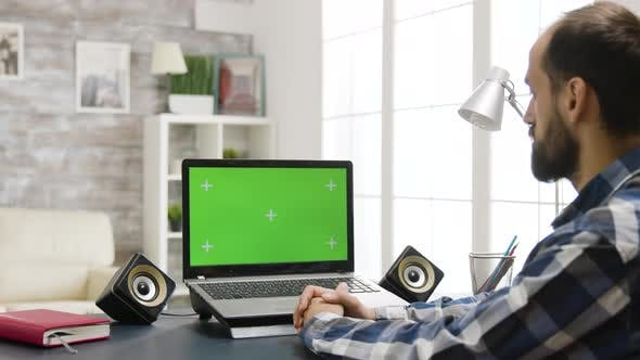 Over the Shoulder Zoom in Shot of Man Looking at Laptop with Green Screen