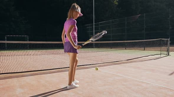 Attractive Female Tennis Player Hitting the Ball to the Ground Using a Racket