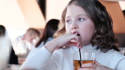 Little girl drinks juice through a straw
