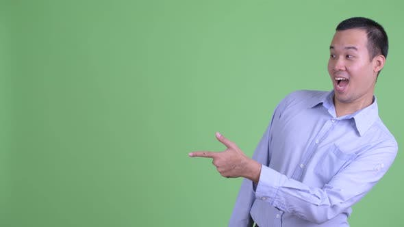 Thumbnail for Happy Asian Businessman Pointing Finger and Showing Something