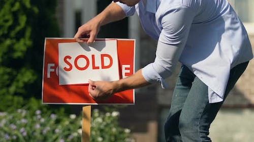 Young Man Setting Sold Sign Front of Building, Property Sell Service, Ownership