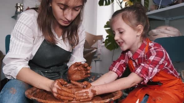 Ceramic Artist Teaching Girl How To Create Ceramics