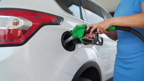 Woman Pulls Out a Refueling Gun From a Car Tank After Finishing Refueling
