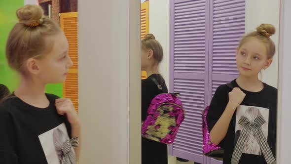 Thumbnail for Girl Trying Stylish Glittering Backpack and Looking at Mirror