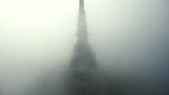 Thumbnail for Drone Rising Above Foggy Clouds To Reveal Epic Golden Statue on Top of Iconic Mont Saint Michel