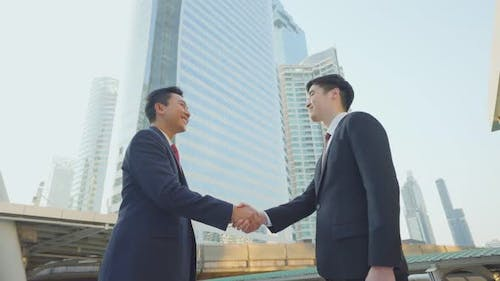 Asian businessman make handshake in city building after business deal agreement in the background.