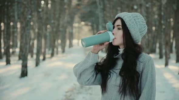 Frau mit Pullover und Hut trinkt heißen Tee im Winterwald