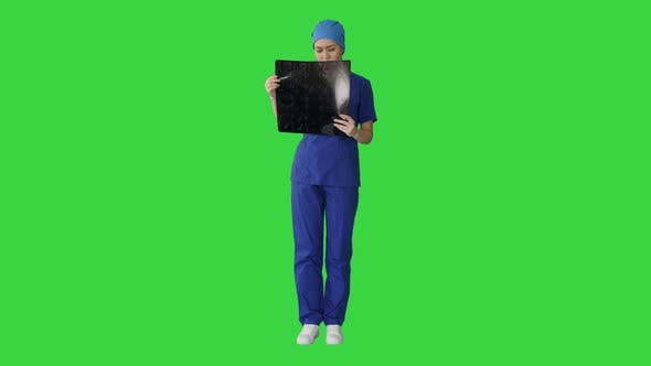 Thumbnail for Serious Female Doctor Looking at MRI Scan of Brain on a Green Screen, Chroma Key