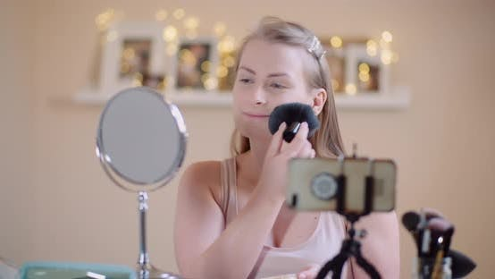 Cover Image for Young Woman Doing Makeup in Front of Mirror at Home