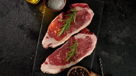 Steak Striploin Raw Beef with Rosemary and Spices Rotates.
