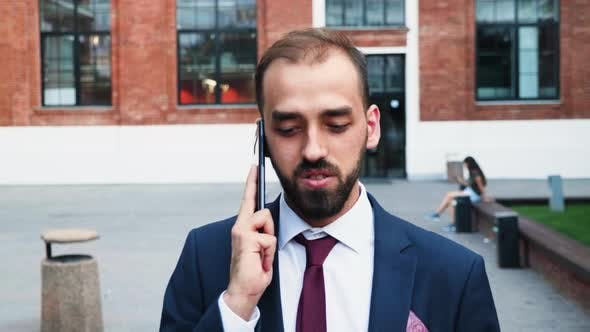 Thumbnail for Businessman in Suit Walking and Talking on the Phone in Front of the Business District