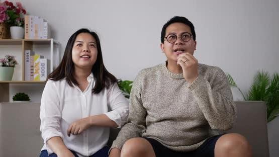 Cheerful couple cheering football game on TV