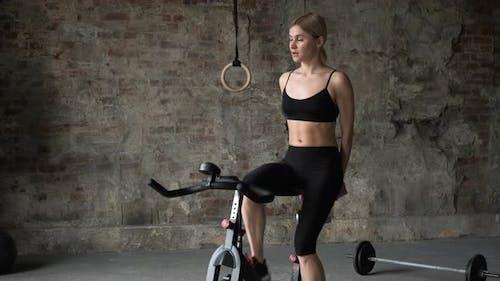 Beautiful fitness women doing exercises on bike in gym. Beautiful fitness women in sportswear