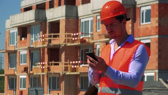 Thumbnail for Construction Worker Works on the Smartphone in Front of Building Site