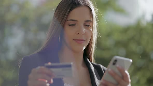 Thumbnail for Smiling Young Woman with Smartphone and Credit Card