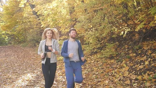 Man and Woman Jogging Through Autumn Forest Happy Young Couple Enjoying Healthy Lifestyle
