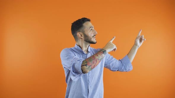 Cover Image for Black Haired Man Pointing with Fingers Up at Invisible Product, Isolated on Orange Background