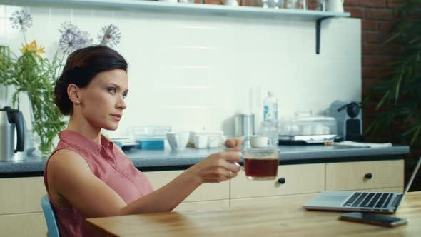 Thumbnail for Businesswoman Watching Laptop with Cup of Tea in Kitchen. Girl Surfing Internet.