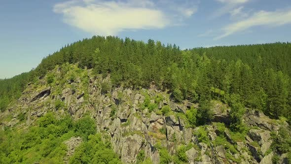 Aerial: Take Off Over the Stone Mountain with Coniferous Forest