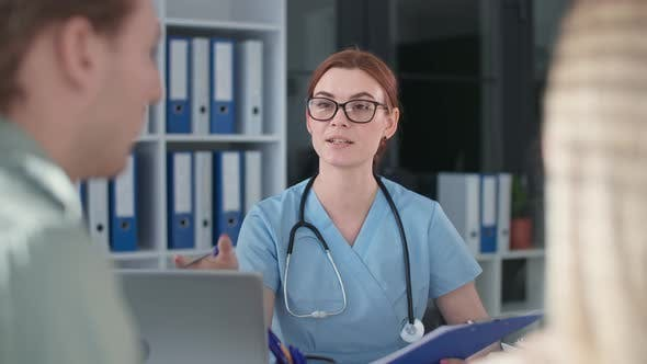 Charming Young Doctor with Glasses and Phonendoscope Reports Good News About Results of Analysis to