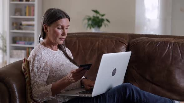 Senior Elderly Woman Buying Online with Credit Card Using Laptop Sit on Couch
