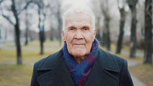 Portrait of grey-haired senior man looking at camera. 90 years old person.
