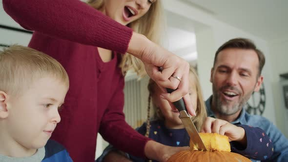Thumbnail for Handheld video shows of family drilling pumpkins for Halloween