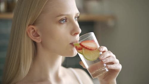 Young Woman Drinks Water with Strawberries and Lemon in the Kitchen